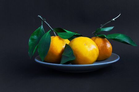 Ripe oranges on a blue plate on a black background. Fresh citrus fruits. concept - healthy food, vitamins, dietary products. Diet. Vegetarian. Close up. copy space