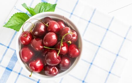 Fresh ripe cherry on a white ceramic plate on a napkin on a wooden white background. The concept of Healthy food and tasty dessert. Diet vegetarian. Close up. Copy space