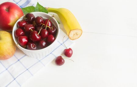 Ripe cherry on a white ceramic plate on a napkin on a wooden white background With cherry berries,apples and bananas. Concept Healthy food and dessert Diet vegetarian Close up. Copy space 写真素材