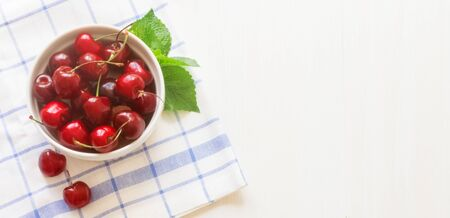 Fresh ripe cherry on a white ceramic plate on a napkin on a wooden white background With cherry berries and bananas The concept of Healthy food and tasty dessert. Diet vegetarian. Close up. Copy space 写真素材