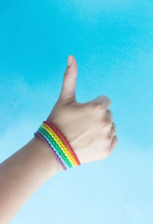Thumbs up. Rainbow bracelet with LGBT symbol on blue background. The symbol of the flag. The concept of gay pride, happiness, freedom and love for same-sex couples.