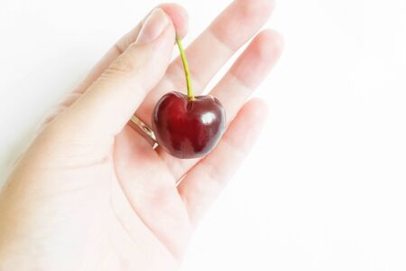 Womans hand holding red ripe cherry on white background. Isolated. ripe fruit. The concept of healthy natural food. Diet. Vegetarian. Vitamins. Natural harvest of fruits and vegetables. copy space