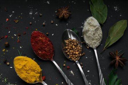 Set of different spices and herbs in metallic shiny spoons on black background. Ingredients pepper, ginger,saffron, chili, cardamom, cinnamon, anise. Concept-Indian, Asian, Turkish cuisine. Top view