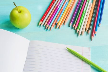 Concept back to school.School accessories, colored pencils, pen, apple with empty notebook on blue wooden background. First of September. drawing. Autumn. Studying at the College. Close up. copy space 写真素材