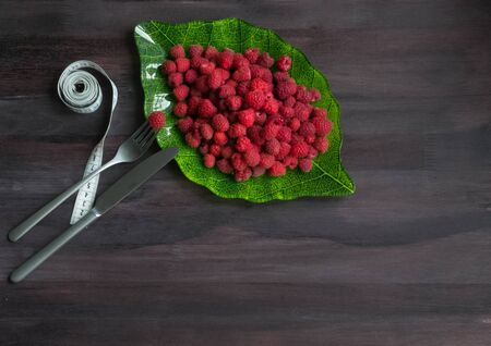 Ripe raspberry in a green leaf plate on a black wooden background with fork, knife and measure tape. Fresh berries. Concept Useful vitamin fruit diet. Natural Breakfast. Vegan. copyspace