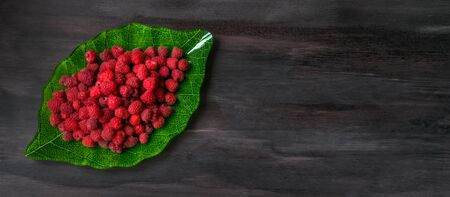 Ripe raspberry in a plate in the form of a green leaf on a black wooden background. Fresh berries. The concept of fresh and natural Breakfast. Useful vitamin diet. Vegetarian.Organic food. copy space