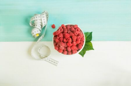 Ripe raspberry in white ceramic cup and measure tape on white-blue background. Concept diet. Losing weight. Ingredients. Healthy dietary proper food. Delicious breakfast. top view. copy space for text