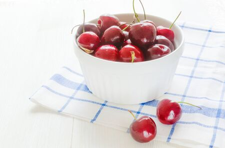 Fresh ripe cherry in white ceramic bowl on napkin on wooden white background.the concept of a Diet. Ingredients of healthy food and delicious dessert. Vegetarian. Summer harvest. Gardening. Close up.