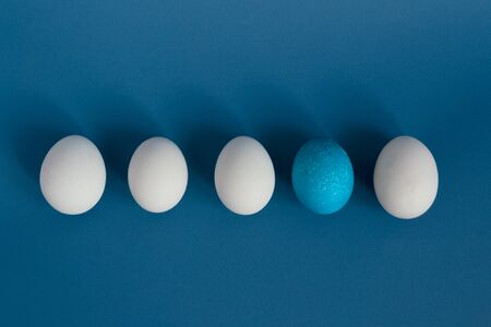 White eggs and blue egg in a row on blue background