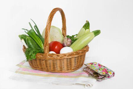 Cibo e generi alimentari in un cestino della spesa in vimini su un tovagliolo su sfondo bianco. Paniere del consumatore. Negozio. Mercato. Vendita