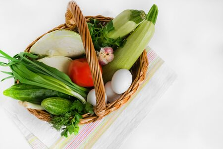 Food and groceries in a wicker shopping basket on a napkin on a white background. Consumer basket. Shop. Market. Sale