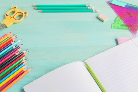 Concept back to school.School accessories, colored pencils, pen with empty notebook on blue wooden background.