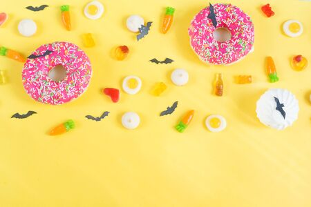 Halloween candy.Halloween holidays on yellow background, colorful decoration toys, baby sweets, donuts, marmalade. trick or treat, terrible night.halloween background Reklamní fotografie