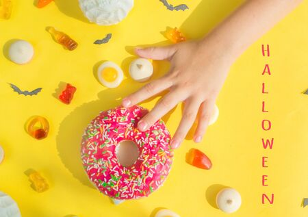 Halloween candy.Halloween holidays on yellow background, colorful decoration toys, baby sweets, donuts, marmalade. The girls hand reaches for the candy.trick or treat, terrible night