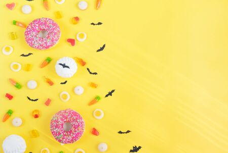 Halloween candy.Halloween holidays on yellow background, colorful decoration toys, baby sweets, donuts, marmalade. trick or treat, terrible night.Halloween background.copy space Reklamní fotografie
