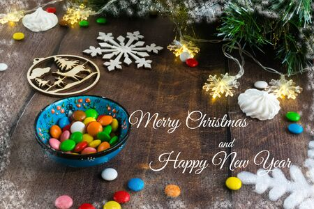 Merry Christmas and happy New year. Christmas decoration design on wooden background with candy bowl.the composition of Christmas tree branches, lights, cones, toys, candy, snowflakes. Foto de archivo - 130805323