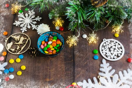 Merry Christmas and happy New year. Christmas decoration design on wooden background with candy bowl.the composition of Christmas tree branches, lights, cones, toys, candy, snowflakes. Foto de archivo - 130805322