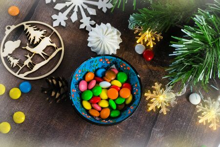 Merry Christmas and happy New year. Christmas decoration design on wooden background with candy bowl.the composition of Christmas tree branches, lights, cones, toys, candy, snowflakes. Foto de archivo - 130805328