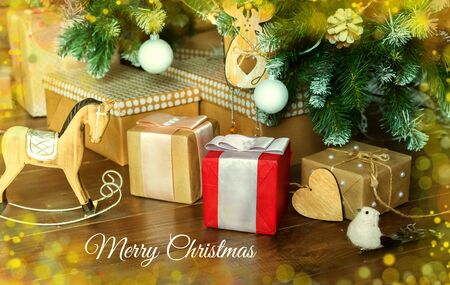 Christmas gifts in different packaging, toys, wooden horse birds and cookies under the branches of the Christmas tree on Christmas eve. Holiday.Decorated the house. Greeting card. text merry christmas Foto de archivo - 133816755