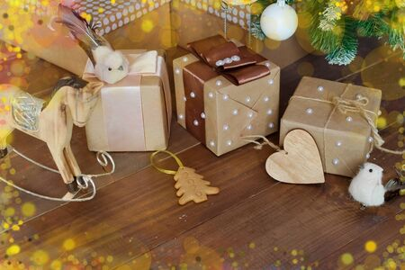 Beautiful Christmas gifts in different packaging, toys, wooden horse birds and cookies under the branches of the Christmas tree on Christmas eve. Holiday.Decorated the house.Greeting card. copy space Foto de archivo - 133816758