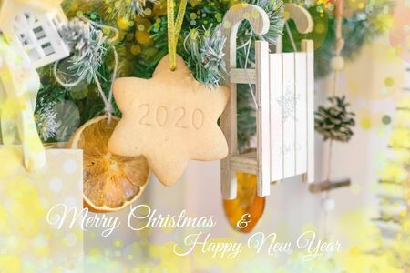 Christmas garland of Christmas tree branches, toys, dried oranges and star shaped cookies. with the number 2020 and the text merry christmas and happy new year Foto de archivo - 133816759