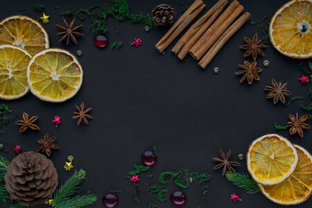 Merry Christmas and happy new year. composition on a black background of Christmas tree branches, cones, toys, cinnamon, dried oranges and anise. Greeting background, card or layout design. copy space
