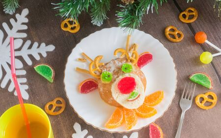 Christmas edible deer of buns and marmalade on a plate on a wooden table next to candy and Christmas tree branches.Kids food.Christmas edible food..Christmas minimalism.