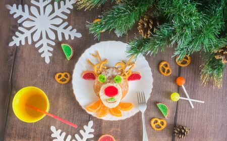 Christmas edible deer of buns and marmalade on a plate on a wooden table next to candy and Christmas tree branches.Christmas kids food.Christmas edible food.Christmas minimalism Stock Photo