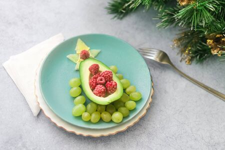 Delicious edible Christmas tree of avocado, frozen sweet raspberries and grapes on a blue plate on the table near the branches of the Christmas tree.Children's Breakfast.new year festive table. Foto de archivo - 132573271