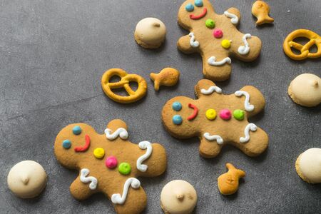 Delicious Christmas gingerbread men.Christmas baking ingredients and supplies on dark background.Congratulation.Cooking. Christmas cookie man.festive garland.Christmas minimalism.close up.copy space. Foto de archivo - 132724234