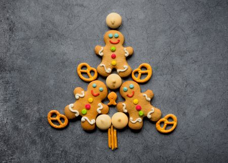 Delicious Christmas gingerbread men in the form of a Christmas tree. Christmas baking ingredients and supplies on dark background. Christmas minimalism.copy space Foto de archivo - 133816779