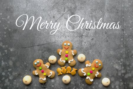 Delicious Christmas gingerbread men.Christmas baking ingredients and supplies on dark background.Postcard. Congratulation.Cooking. Christmas minimalism.copy space Foto de archivo - 133816774