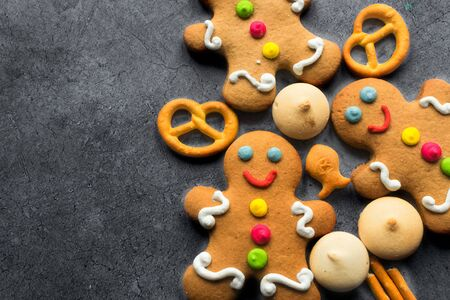 Delicious Christmas gingerbread men.Christmas baking ingredients and supplies on dark background.Congratulation.Cooking. Christmas cookie man.festive garland.Christmas minimalism.close up.copy space. Foto de archivo - 132726672