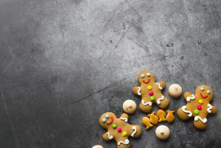 Delicious Christmas gingerbread men.Christmas baking ingredients and supplies on dark background.Postcard. Congratulation.Cooking. Christmas minimalism.copy space Foto de archivo - 133816778