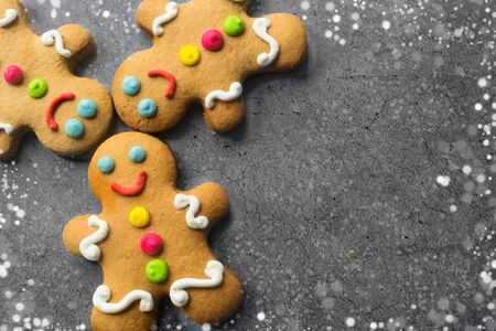 Delicious Christmas gingerbread men.Christmas baking ingredients and supplies on dark background.Congratulation.Cooking. Christmas cookie man.festive garland.Christmas minimalism.close up.copy space. Foto de archivo - 132810075