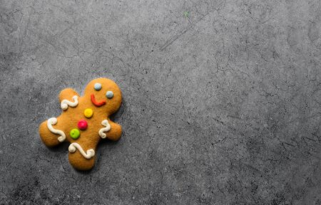 Delicious Christmas gingerbread men.Christmas baking ingredients and supplies on dark background.Postcard. Congratulation.Cooking. Christmas cookie man.Christmas minimalism.close up.copy space Foto de archivo - 133816821