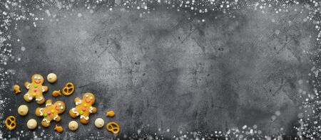 Delicious Christmas gingerbread men.Christmas baking ingredients and supplies on dark background.festive garland.Congratulation.Cooking. Christmas minimalism.Christmas cookie man.banner.copy space. Foto de archivo - 133232445