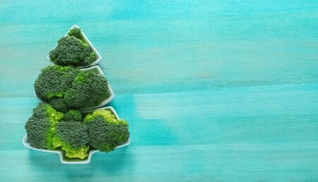 Creative edible Christmas tree made of fresh broccoli.Holiday ideas. New year food background top view . holiday, celebration, food art concept Foto de archivo - 133816828