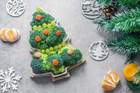 Creative edible Christmas tree of fresh broccoli next to Christmas tree and tangerines.Concept: vegan holiday ideas.Healthy food.New year food background.top view.Holiday,celebration, food art concept Foto de archivo - 133322470