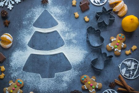 Christmas tree made from flour on a dark table with cookies, tangerines, anise and cinnamon, chocolate and cookie cutters. Concept Christmas baking. Cooking on Christmas Eve. Top view. Copy space Foto de archivo - 133322698