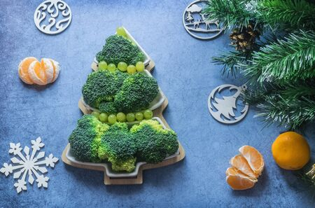 Creative edible Christmas tree made of fresh broccoli.Holiday ideas. New year food background top view . holiday, celebration, food art concept Foto de archivo - 133816831