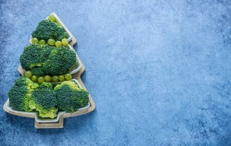 Creative edible Christmas tree of fresh broccolion on a blue background.Vegan holiday ideas.Healthy food.New year food background.Holiday,celebration, food art concept.Minimalism.Top view.Copy space Foto de archivo - 133333512
