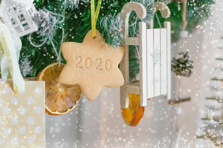 Garland of Christmas tree branches, toys, dried oranges and star shaped cookies. with the number 2020 Foto de archivo - 133816833