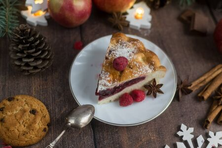 Delicious Christmas raspberry pie with berry filling and icing sugar and spices on a dark background. Foto de archivo - 133816848