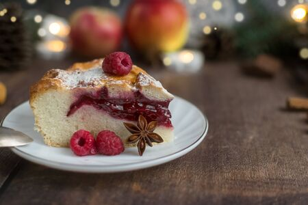 Delicious Christmas raspberry pie with berry filling and icing sugar and spices on a dark background. Foto de archivo - 133816850