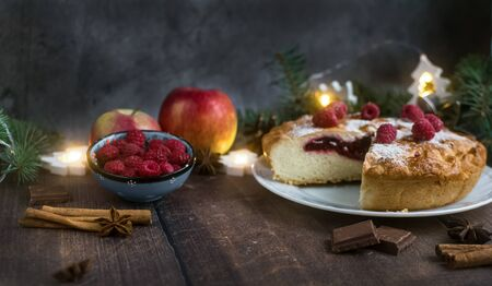 Delicious Christmas raspberry pie with berry filling and icing sugar and spices on a dark background. Foto de archivo - 133816852