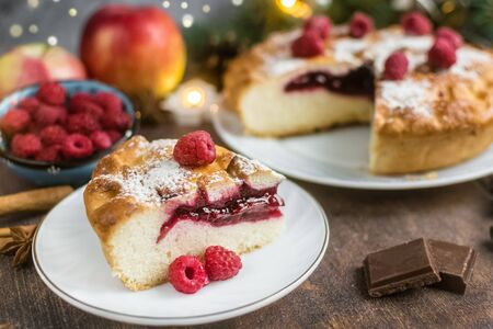 Delicious raspberry pie with berry filling and icing sugar and spices for Thanksgiving or Christmas on a dark background.Next to apples,chocolate and garlands. A party.dinner.Festive dinner.Close up Foto de archivo - 133816857