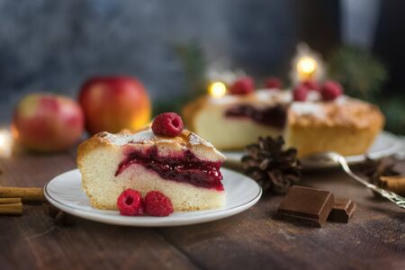 Delicious raspberry pie with berry filling and icing sugar and spices for Thanksgiving or Christmas on a dark background.Next to apples,chocolate and garlands. A party.dinner.Festive dinner.Close up Foto de archivo - 133816861