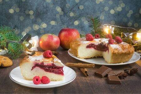 Delicious raspberry pie with berry jam, icing sugar and spices for Thanksgiving or Christmas on dark background.Christmas lights.Apples, chocolate, garlands.Festive dinner.Christmas eve.Party.Close up Foto de archivo - 133816874