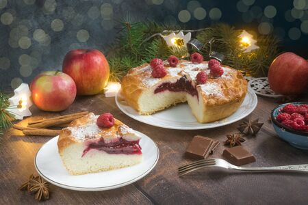 Delicious raspberry pie with berry jam, icing sugar and spices for Thanksgiving or Christmas on dark background.Christmas lights.Apples, chocolate, garlands.Festive dinner.Christmas eve.Party.Close up Foto de archivo - 133816873